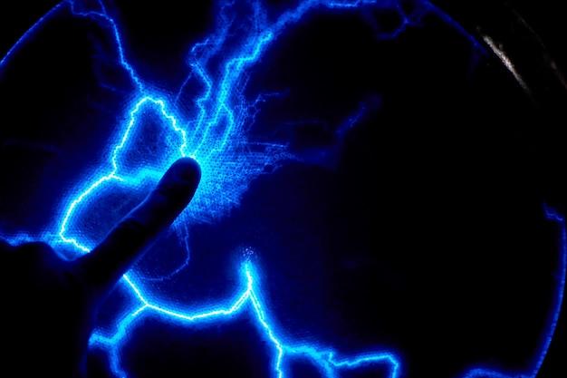Sfera di plasma elettrico dito tocco su uno sfondo scuro. modello elettrico statico