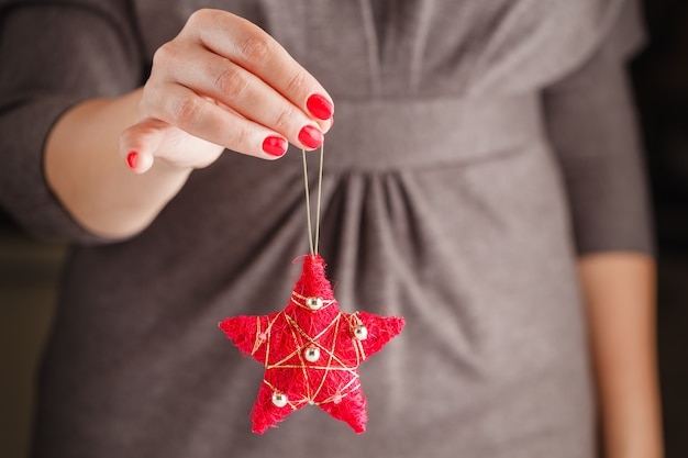 Sfera rossa del giocattolo di natale della holding della donna
