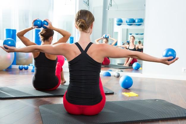 Sfera tonificante blu nella vista posteriore della classe dei pilates delle donne