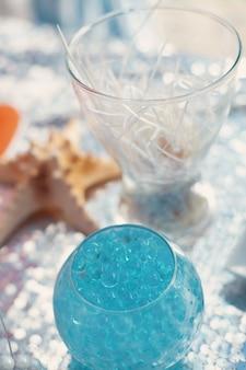 Sfere blu luminose nel vaso di vetro. tema di seatime sul candybar della festa.