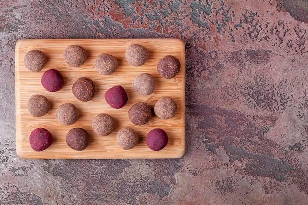 Sfere crude casalinghe di energia del cacao del vegano sul vassoio di legno