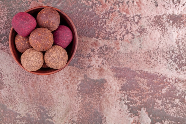 Sfere crude variopinte casalinghe di energia del cacao del vegano in ciotola di legno