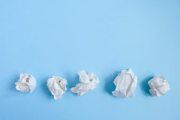 Sfere di carta sgualcite sul blu. idea concettuale e creativa