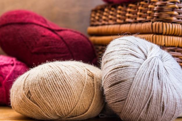 Sfere di clews di filato di lana grigio beige rosso naturale, cesto di vimini