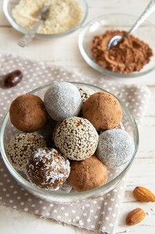 Sfere di energia con cacao e semi di sesamo in una ciotola di vetro su un bianco