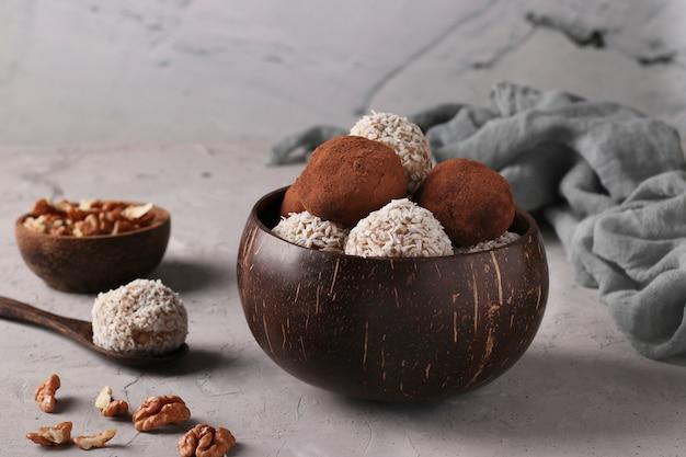 Sfere di energia di noci e farina d'avena con scaglie di cocco e cacao in ciotola di cocco sulla superficie grigia, formato orizzontale, primo piano