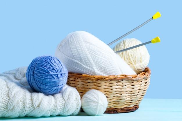 Sfere di filato bianco e blu, ferri da maglia e un maglione lavorato a maglia bianco. concetto di maglieria. maglieria e abbigliamento invernale