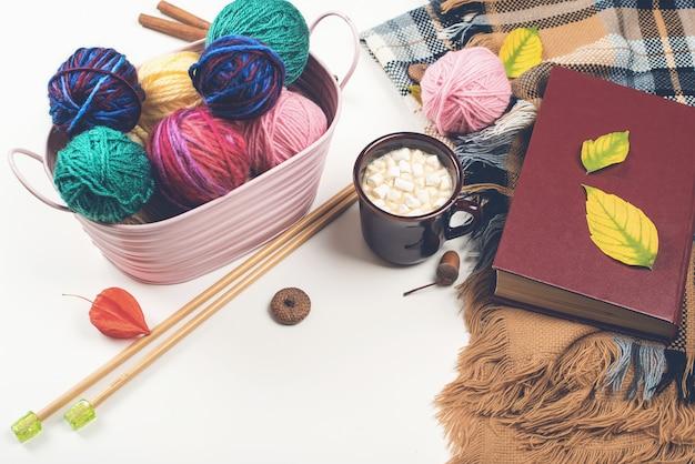 Sfere di filato di lana naturale e ferri da maglia in legno sul tavolo bianco