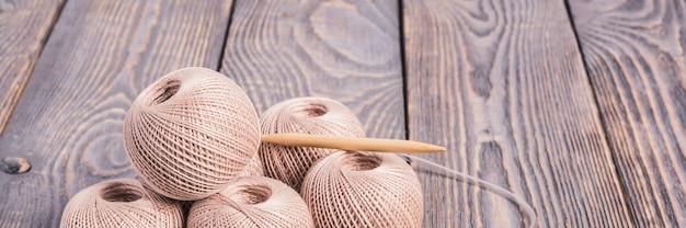 Sfere di filato e ferri da maglia per lavorare a maglia su di legno.