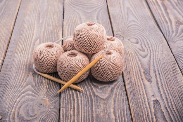 Sfere di filato e ferri da maglia per lavorare a maglia su un fondo di legno.