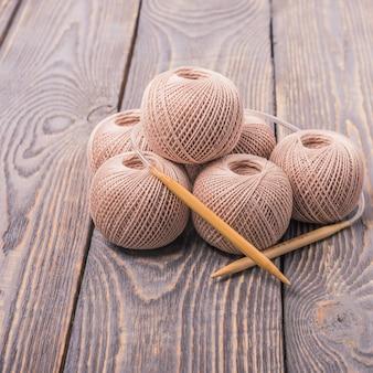 Sfere di filato e ferri da maglia per maglieria su un fondo di legno.