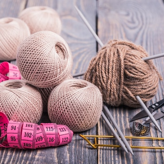 Sfere di filato, ferri da maglia e nastro di misurazione su un fondo di legno.