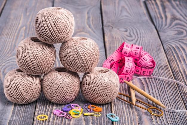 Sfere di filato, ferri da maglia, nastro di misurazione e clip su fondo di legno