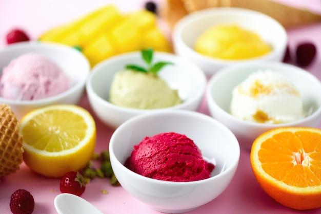 Sfere di gelato rosso, viola, giallo, verde, in ciotole, coni di cialda, bacche, arancia, mango, limone, menta, pistacchio
