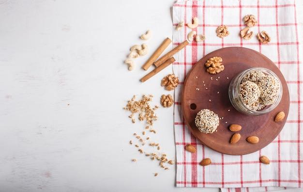 Sfere di palline energetiche con mandorle, sesamo, anacardi, noci, datteri e grano germinato in barattolo di vetro, vista dall'alto.