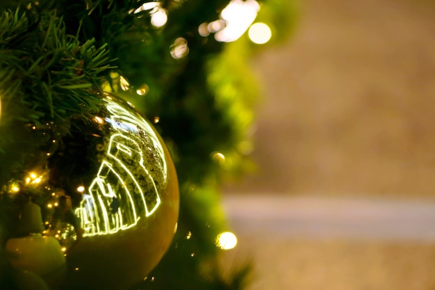 Sfere dorate di natale del primo piano decorate sull'albero di pino il giorno di natale con bokeh di illuminazione principale e fondo confuso.