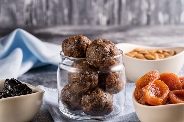 Sfere energetiche di frutta secca e noci in un barattolo di vetro, accanto agli ingredienti per la cottura di albicocche secche, prugne secche, mandorle.