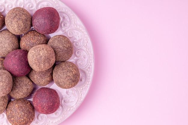 Sfere energetiche fatte in casa di cacao crudo vegano, caramelle al cioccolato salutari di noci, datteri