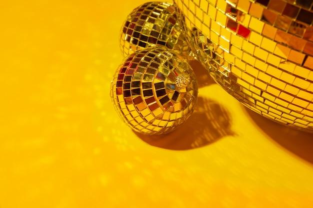 Sfere lucide della discoteca del partito che splendono in una luce di giorno sopra la priorità bassa di colore