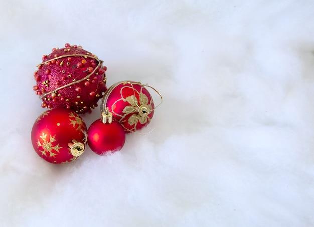 Sfere rosse di natale sulla priorità bassa della neve