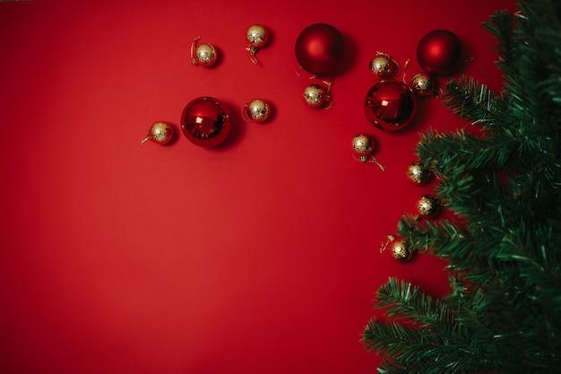 Sfere rosse e dorate di natale ed albero di natale verde