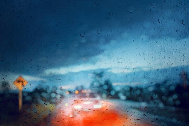 Sfocata di strada di campagna, vista attraverso lo scudo del vento della tempesta di pioggia / condizioni meteorologiche avverse, in scena notturna.