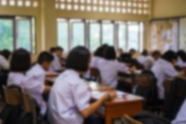Sfocato di studenti delle scuole superiori del gruppo asiatico con uniformi in aula, attività di studio