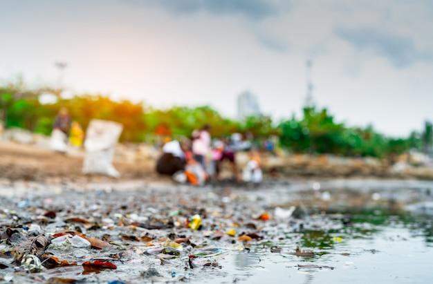 Sfocato di volontari che raccolgono immondizia. inquinamento ambientale da spiaggia. volontari che puliscono la spiaggia. riordinare la spazzatura sulla spiaggia. macchie d'olio sulla spiaggia.