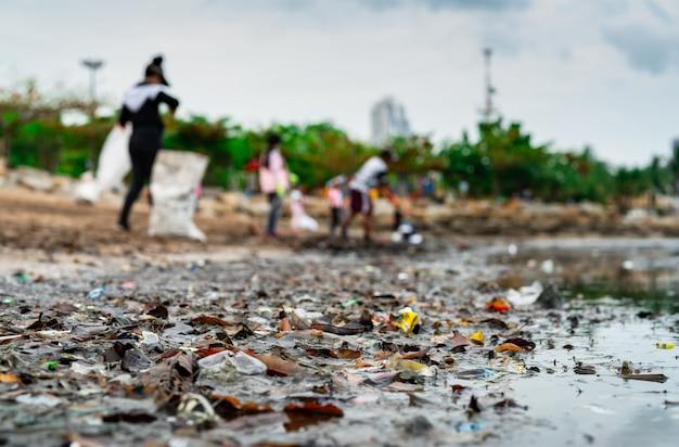 Sfocato di volontari che raccolgono rifiuti. inquinamento ambientale della spiaggia