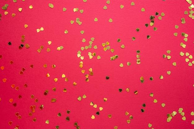Sfocato, sfocato astratto natale astratto sfondo rosso con glitter a forma di cuore d'oro. san valentino piatto disteso.