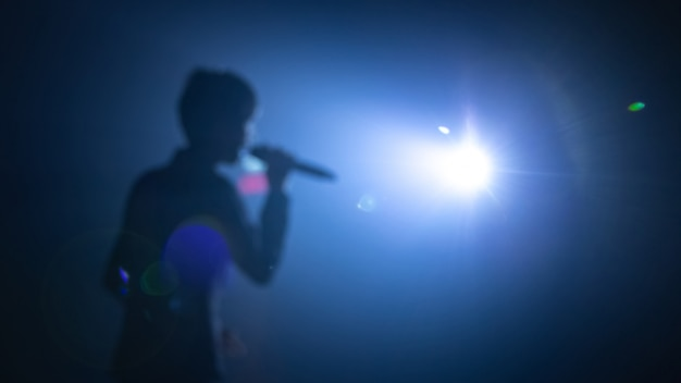 Sfocato sullo sfondo del cantante sul palco del concerto