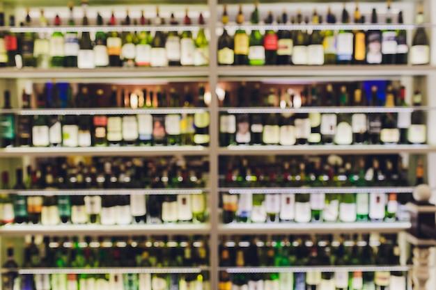 Sfocato sullo sfondo sfocato dello scaffale del vino. le bottiglie giacciono sulla paglia. cantina. sfocato sfocato