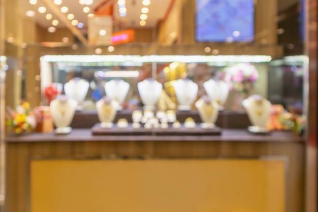 Sfocatura astratta dell'esposizione della finestra del negozio di diamanti dei gioielli dell'oro con il fondo della luce del bokeh