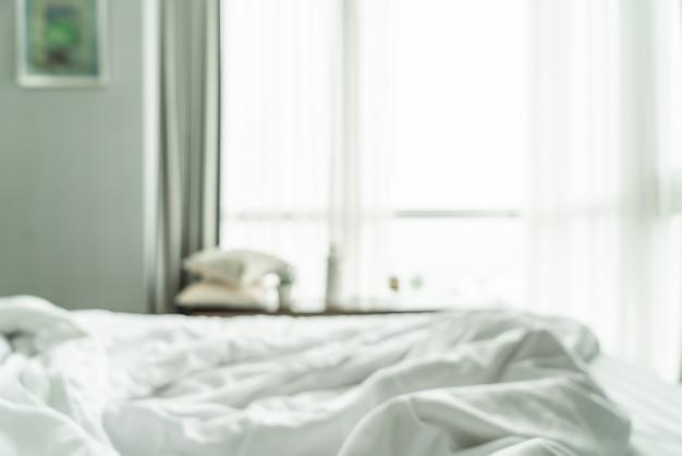 Sfocatura astratta letto disordinato con tenda e finestra