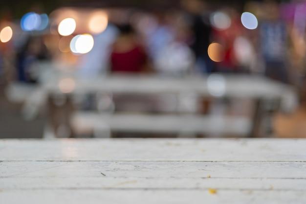 Sfocatura colore sfondo completo con tavolo in legno bianco in primo piano durante la notte.