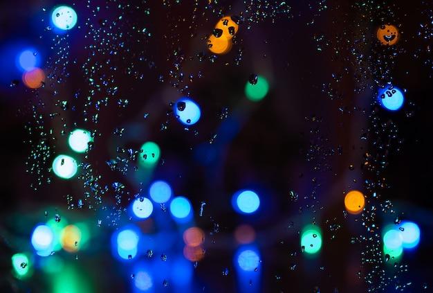 Sfocatura gocce di pioggia nella finestra di notte