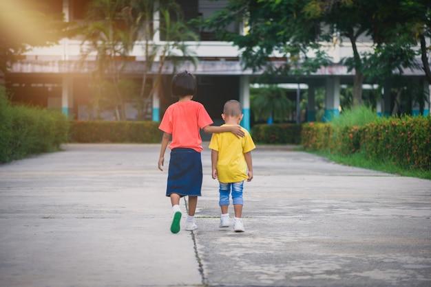 Sfocatura sfondo fratelli e sorelle camminano mano nella mano