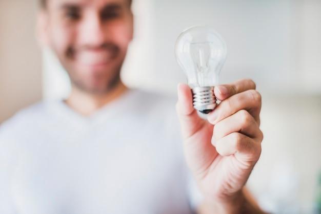 Sfocatura uomo che mostra la lampadina trasparente