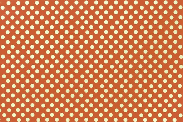 Sfondo arancione chiaro da carta da imballaggio con una di pois dorati