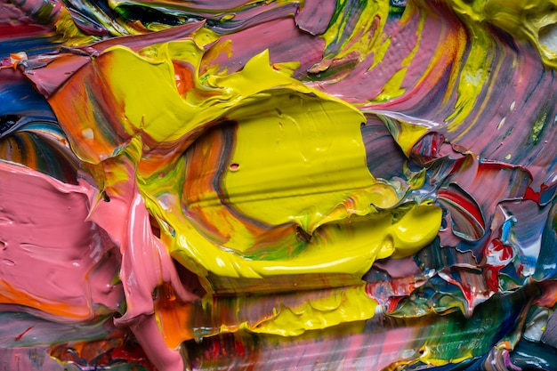 Sfondo artistico. diversi colori brillanti di colori ad olio sono mescolati su un primo piano tavolozza.