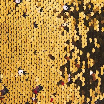 Sfondo astratto con paillettes oro colore sul tessuto
