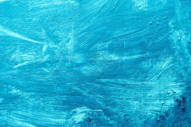 Sfondo astratto con tratti strutturati di vernice blu sulla superficie in legno.