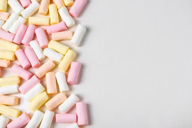 Sfondo astratto con un sacco di marshmallow colorati di rosa, bianchi e gialli. disteso in piano