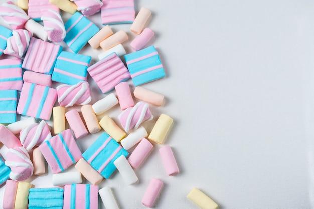 Sfondo astratto con un sacco di marshmallow colorati di rosa, blu e gialli. disteso in piano