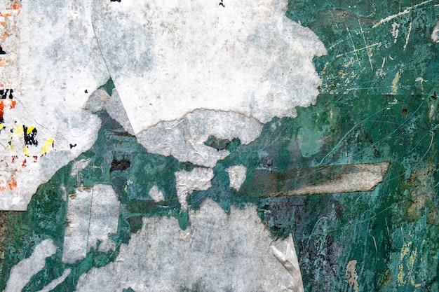 Sfondo astratto da parete colorata con carta adesiva strappata.