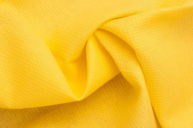 Sfondo astratto di tessuto giallo brillante. pieghe, pieghe del tessuto di cotone. modello materiale, trama del panno. onde su carta da parati.