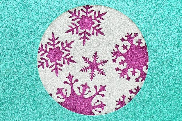 Sfondo astratto e trama di un materiale lucido blu con un foro rotondo, all'interno del foro c'è un materiale d'argento con fiocchi di neve ritagliati su uno sfondo viola lucido.