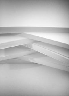 Sfondo astratto, minimalismo. diverse pile di carta bianca per fotocopiatrice, su uno sfondo bianco. concetto di lavoro d'ufficio.