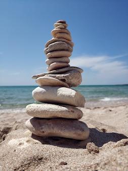 Sfondo astratto torre di pietra su una spiaggia di ciottoli