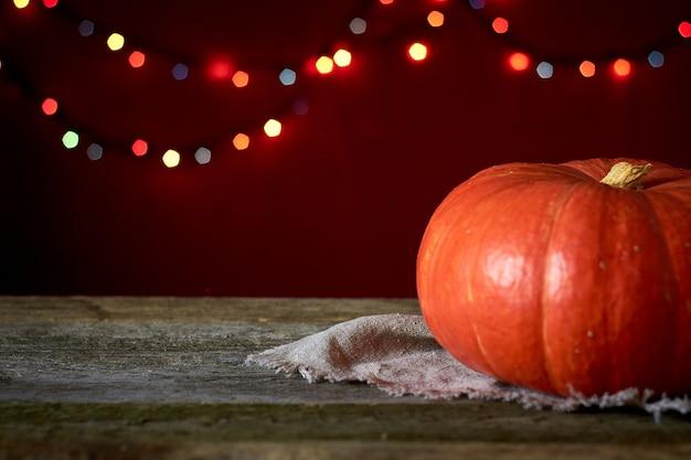 Sfondo autunnale su una superficie di legno scuro, zucca arancione su uno sfondo di luci sfocate